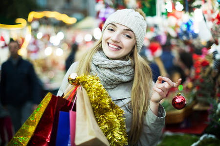 Smiling girl in coat posing at Chrisrmas market  in evening
