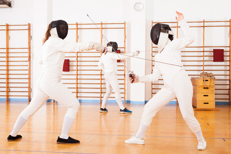 active female athletes in uniform practicing movements at fencing battle