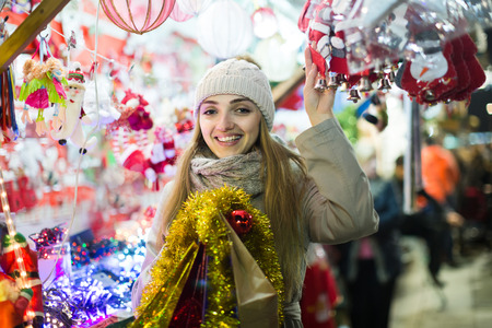Smiling european woman shopping at Christmas fair before Xmas in evening time
