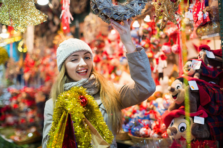 Beautiful smiling woman choosing Christmas decoration at market in evening time