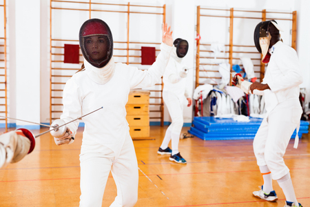 Two glad cheerful positive smiling female fencers  exercising movements in duel at fencing room