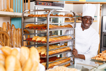 Portrait of happy successful baker in white uniform working in small bakery