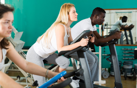 Positive man and two women in sportswear training on exercise bikes at sport club