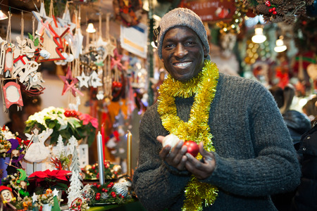 Cheerful African American looking for New Year decorations in traditional street market