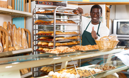 Smiling African American baker wearing apron giving thumbs up while working behind counter in small bakery Foto de archivo