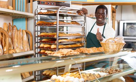 Uśmiechnięty afroamerykański piekarz noszący fartuch pokazujący kciuk w górę podczas pracy za ladą w małej piekarni Zdjęcie Seryjne