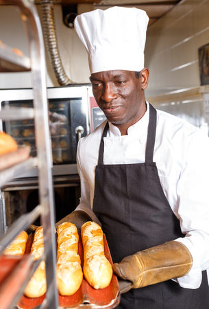 Experienced baker working in small bakery, taking out bread from industrial oven and putting on rack