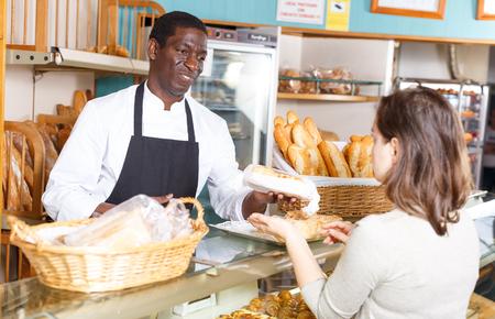 Polite male baker working behind counter in store of his bakery, serving female customer 版權商用圖片