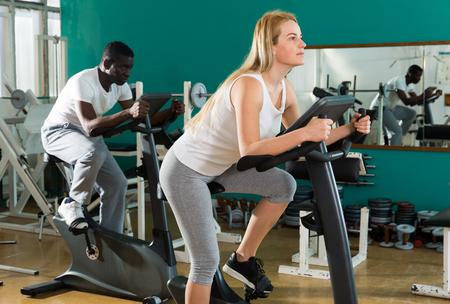 Portret van paar training op stationaire cycli bij sportclub