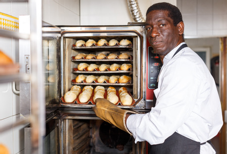 Professional baker checking readiness of baguettes in bread oven