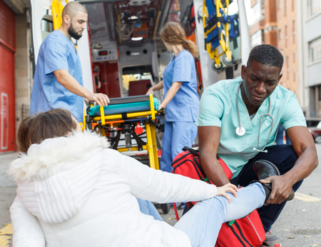 Emergency doctors providing first aid to injured woman near ambulance car