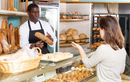 Polite male baker working behind counter in store of his bakery, serving female customer