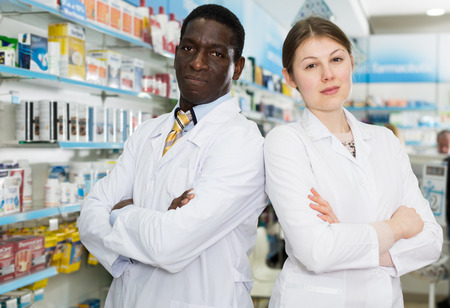 Positive male and female pharmacists standing in interior of modern pharmacy 免版税图像