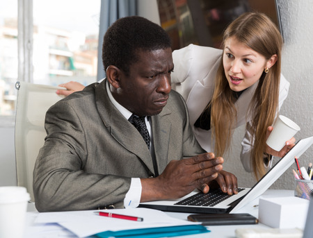 Young Caucasian businesswoman flirting with African American male colleague during work in modern coworking space