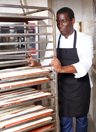 African American worker of bakery preparing dough products for next baking in professional bread oven 版權商用圖片