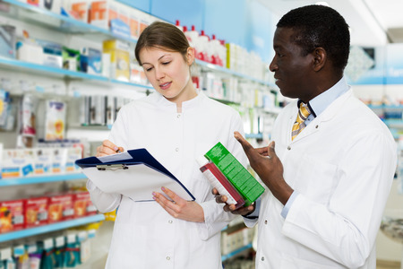 Experienced young male and female pharmacists taking inventory of medicines in pharmacy