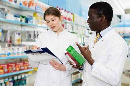 Farmacéuticos masculinos y femeninos jóvenes con experiencia haciendo inventario de medicamentos en farmacia