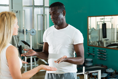 Positive man and woman in sportswear having conversation at sport club