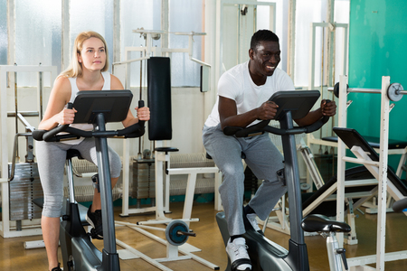 Positive man and woman in sportswear training on exercise bikes at sport club