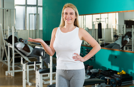 Portrait of young woman in sportswear welcoming to sport club Stock Photo