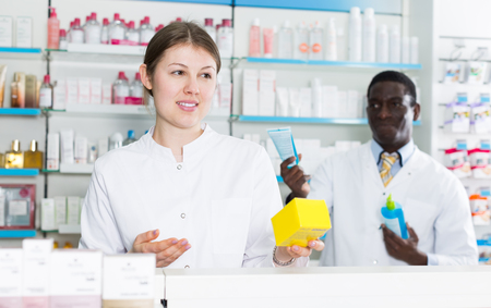 Apothecary female recommending medicinal product in pharmacy