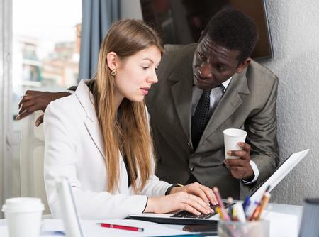 Fokussiertes internationales Geschäftsteam, das in einem modernen Büro mit Computern arbeitet Standard-Bild