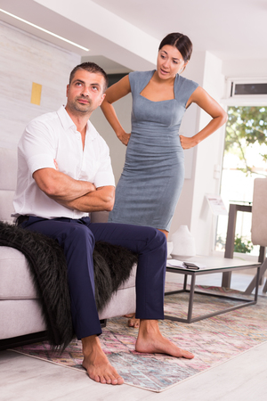 Offended young man sitting on sofa at home with disgruntled woman behind