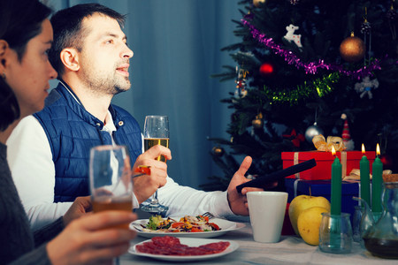 Family celebrate the New Year with champagne and watching tv in home interior