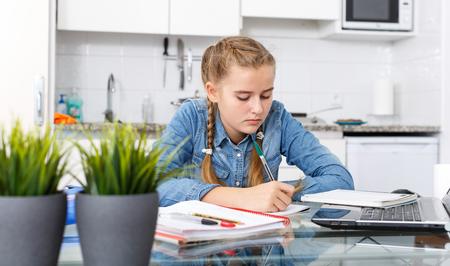 Portrait of teenage girl doing herself her home task using laptop in kitchen Standard-Bild