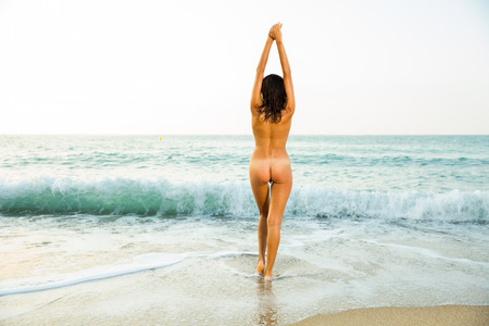 Back view of girl playfully posing on the sandy beach