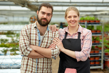 Portrait of positive man and woman gardeners standing in greenhouse