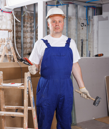 Portrait of construction worker ready for building and repair works indoors
