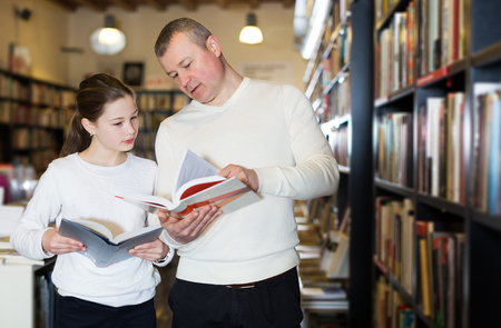 Positive man with daughter looking for interesting books in library