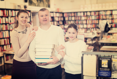 Loving attractive parents and happy girl standing with stack of books in hands in bookshop