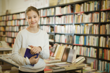 Portrait of cheerful positive  preteen girl holding thick book in bookstore interior
