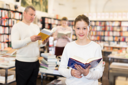 Intelligent little girl visiting a bookstore with parents searching interesting books Imagens - 121878405
