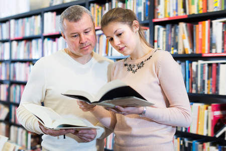 Positive couple choosing and discussing books in bookshop
