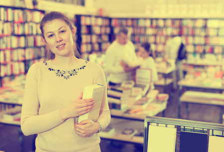 Portrait of attractive young  girl holding thick book in bookstore interior