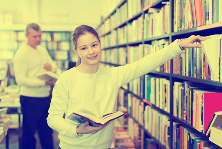 cheerful schoolgirl standing in library with  books in hands