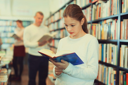 Portrait of intelligent cheerful  preteen girl browsing textbooks in public library