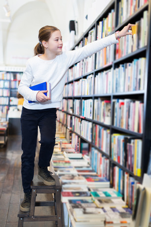 Intelligent girl climbing wooden stepladder for taking book from tall bookcase in shop
