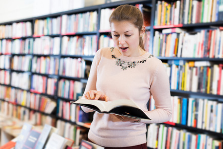 Portrait of surprised adult woman holding open book in bookshop