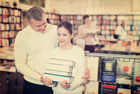 Portrait of glad c tweenage girl with father standing in library with pile of books in hands