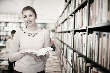 Positive young woman looking for information in books at a bookstore Stok Fotoğraf