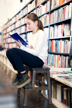 Preteen girl sitting on small wooden step ladder browsing textbook in the library Stok Fotoğraf