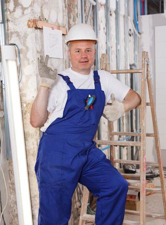 Happy confident professional builder posing in repairable room