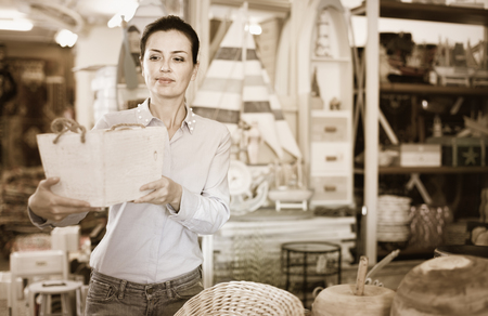 Happy cheerful positive woman standing with wooden box in decoration and furniture store