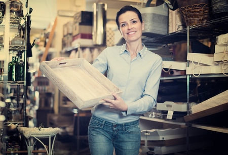 purchaser smiling holding a wooden boxes  shopping at the interior store