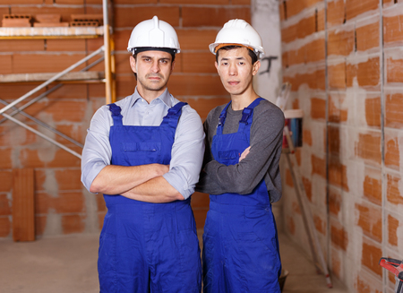 Portrait of two confident workers in uniform inside brick cottage