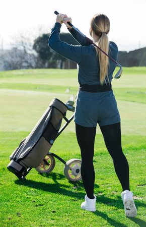 Young spanish woman golfer propelled ball successfully at golf course